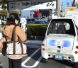 This picture taken on Dec 3, 2014 shows a woman taking a picture of an ultra-compact electric vehicle parking at a Ha:mo (Harmonious Mobility Network) RIDE station in front of Toyota City hall, Aichi prefecture. Toyota is at work developing a community network called Ha:mo for optimal use of cars and other personal vehicles in combination with public transportation. - AFP