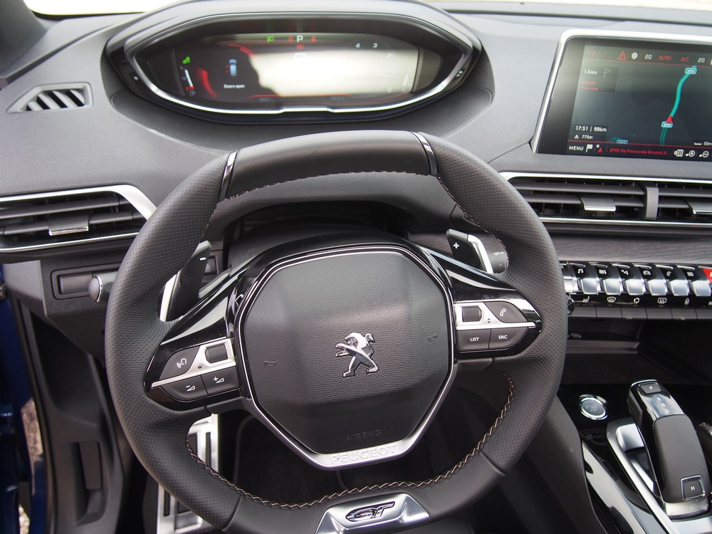 The driver sees over the top of the small steering wheel into the digital instrumentation.