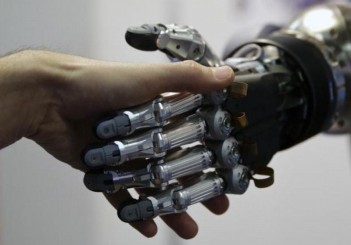 A man shakes hands with a humanoid robot during the International Conference on Humanoid Robots in Madrid