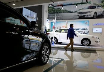 FILE PHOTO:  A man walks at an electric car dealership in Shanghai
