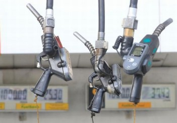 Fuel pumps hang at a gasoline station in Metro Manila